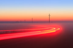 Long Exposure Red Car light trails on a road outside at foggy night on blue hour Royalty Free Stock Image