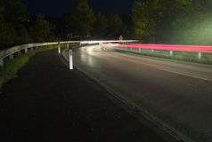 Traffic at Night - Red and White Light Trails around a Highway Corner royalty free stock images