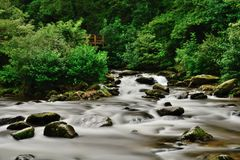 Watersmeet in Devon. Long exposure of the river flowing under the bridge at Watersmeet in Devon royalty free stock photography