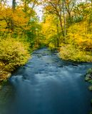Long-exposure of a river running through a colorful Autumn scene in rural Upstate New York, Sleepy Hollow, NY, USA royalty free stock images