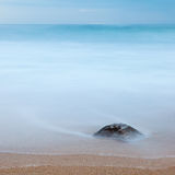 Long Exposure: Rock on the beach. Photo of a rock on a beach, buried in the sand and covered by the ocean. Long exposure. Copy space royalty free stock photography