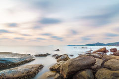 Long exposure rock beach at small island. And smoothe clouds Stock Images