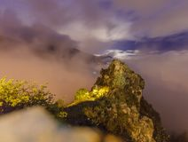 Long exposure of a rock in the french alps, lit by the moon and a streetlight. royalty free stock images