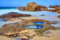 Long exposure rocks and rock pools at low tide Stock Photo