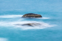Long exposure of rocks in the sea Royalty Free Stock Images