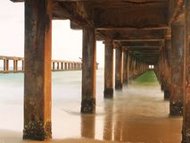The long exposure scene of the sea and details under the old bridge at the sunrise stock image