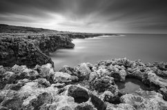 Long exposure of sea and sky, Apulia - Italy. Black and white photography of sky, sea and cliff at sunrise Royalty Free Stock Images