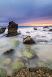 Long exposure seascape during blue hour sunset with rocks as for royalty free stock photography
