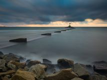 Long exposure seascape with stone breakwater Royalty Free Stock Image