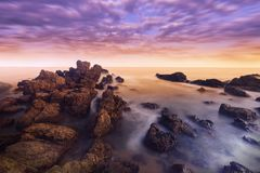 Long exposure of seascape, Sunset in Thailand. Scenic view of rocky beach, Long exposure of the wave during sunset on the beach stock photography
