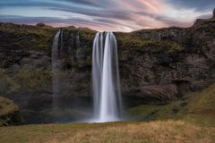 Long exposure of Seljalandsfoss Waterfall. Scenic view of lenticular clouds at sunrise and Seljalandsfoss waterfall in Iceland stock photo