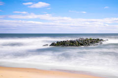 Long exposure shoreline rocks. Long exposure daytime stock photo of rocks off the shoreline of beach in Spring Lake, New Jersey on sunny morning Royalty Free Stock Photo