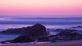 Free Long Exposure Shot At Dusk Over Ocean With Rocks In Foreground And Milky Waves Behind. Stock Photo - 143552860