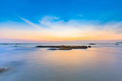 Long exposure shot of calmness sea and the rock in sunset. Long exposure shot of calmness sea and the rock in beautiful sunset sky Royalty Free Stock Photos