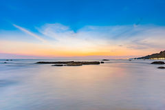 Long exposure shot of calmness sea and the rock in sunset Royalty Free Stock Photo