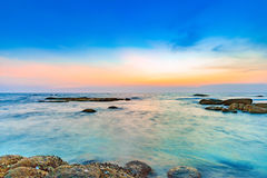 Long exposure shot of calmness sea and the rock in sunset Royalty Free Stock Photography