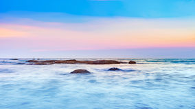 Long exposure shot of calmness sea and the rock in sunset. Long exposure shot of calmness sea and the rock in beautiful sunset sky Stock Photos