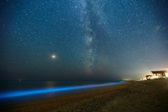 Long exposure shot of glowing plankton on sea surf and milky way. Blue bioluminescent glow of water under the starry sky. Bright Mars planet among royalty free stock image