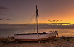 A Long exposure shot of a Greek stranded fishing boat on the beach during sunset. Royalty Free Stock Image
