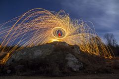 Long exposure shot of man standing on rocky hill spinning steel. Wool in circle making firework showers of bright yellow glowing sparkles on blue night sky royalty free stock images