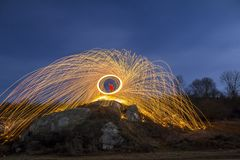 Long exposure shot of man standing on rocky hill spinning steel wool in circle making firework showers of bright yellow glowing sp. Arkles on blue night sky stock photos