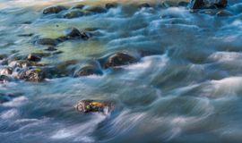 Long exposure shot of Olt river in Transylvania, Romania, focus on the rock royalty free stock image