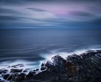 Long exposure shot of rocky seashore coast at dawn after sunset, Russia stock photo