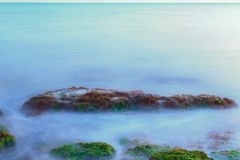 Long Exposure Shot of Sea And Rocks with Seaweeds. Ethereal long exposure shot of sea waves and rocks with green and brown seaweeds stock photography