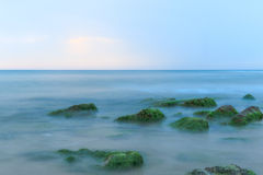Long Exposure Shot of Sea And Rocks with Seaweeds. Ethereal long exposure shot of sea waves and rocks with green and brown seaweeds stock image