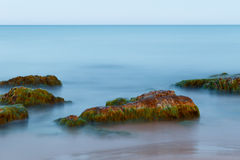 Long Exposure Shot of Sea And Rocks with Seaweeds. Ethereal long exposure shot of sea waves and rocks with green and brown seaweeds royalty free stock photography