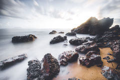 Long exposure shot of a seascape with beautiful rocks in the foreground. Stock Photography