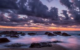 Long exposure shot of the sunset on the beach with rocks and clouds.South Corfu Greece Royalty Free Stock Photography