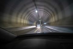 Long exposure shot of tunnel at Lofoten from inside a car that is moving so the light creates tunnel vision effect. Car driving towards stock photo