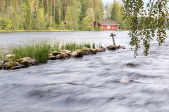 Long exposure shot of a wooden cross by a streaming river Royalty Free Stock Photos