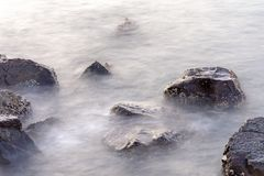 Mystical Rocks in the Sea in Muscat, Oman. A long exposure shows the mystical looking water stream around the wet barnacle filled rocks in Muscat, Oman royalty free stock images
