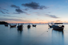 Long exposure silhouette long tail boats with sunrise sky in Koh Lipe Island Stock Photos
