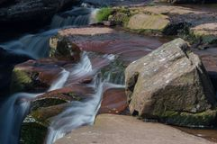 A long exposure of small waterfall cascade over green and brown rocks stock photography