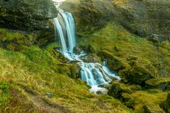 Long exposure of a small waterfall running through a green moss royalty free stock photography