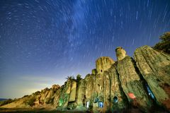 Star trails over rocky cliffside stock image