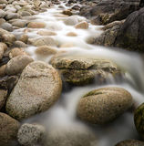 Long exposure stream over rocks to beach. Water worn ancient rocks detail on secluded beach Stock Photo