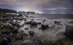 Long exposure of a stunning rocky beach in Odessa at dusk. City lights of the central part of town royalty free stock images