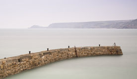 Long exposure sunset image of harbour wall curving into image Royalty Free Stock Photo