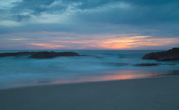 Long exposure at sunset over the rocks at the beach Royalty Free Stock Photography