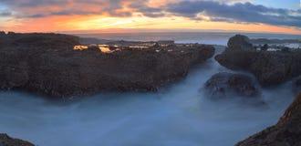 Long exposure of sunset over rocks Stock Photo