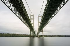 A long exposure of the Tacoma Narrows bridge from underneath at the riverside beach. A long exposure water and the Tacoma Narrows bridge from underneath at the royalty free stock photos