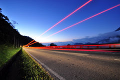 Long exposure of tail light on a highway during twilight Stock Photo