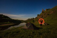 Long exposure of tourist written with burning stick near tents a royalty free stock photography