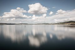 Long exposure view of a lake with moving white clouds perfectly. Reflecting on water Royalty Free Stock Photography