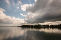 Long exposure view of a lake with moving white clouds perfectly. Reflecting on water Royalty Free Stock Photos