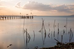 Long exposure view of a pier on a lake at sunset, with beautiful. Warm tones, perfectly still water and fishing nets and poles in the foreground Royalty Free Stock Photo